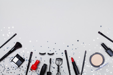 Set of professional decorative cosmetic and makeup tools decorated star confetti on gray table top view. Flat lay composition.