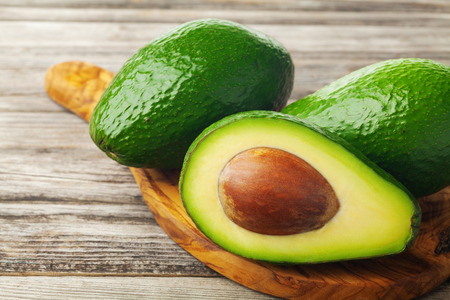 Avocado half and whole on wooden table. Healthy dietary fruit.