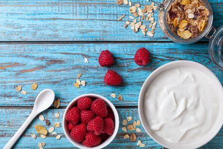 Healthy breakfast with greek yogurt, raspberries and muesli on blue wooden table top view.