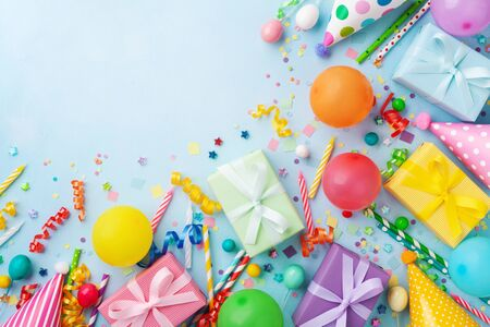 Gift or present boxes, balloons, holiday supplies and confetti on blue table top view. Birthday party greeting card.