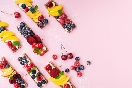 Low calorie snack or dessert from sandwiches with creamy cheese and summer berry fruits on pink trendy background top view. Flat lay. Stok Fotoğraf