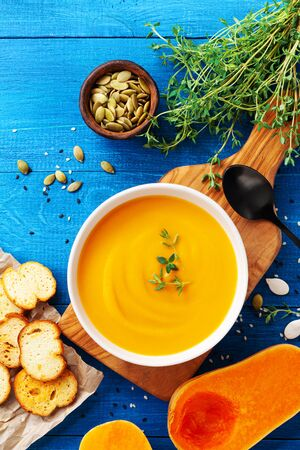 Autumn pumpkin cream soup in bowl served with seeds and crouton on wooden table top view.
