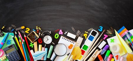 Set of stationery, alarm clock and supplies on blackboard background. Back to school concept. Banner format. Top view. Imagens