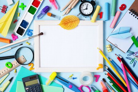 Wooden frame, alarm clock, different stationery and colorful supplies on blue background. Back to school concept. Top view. Imagens