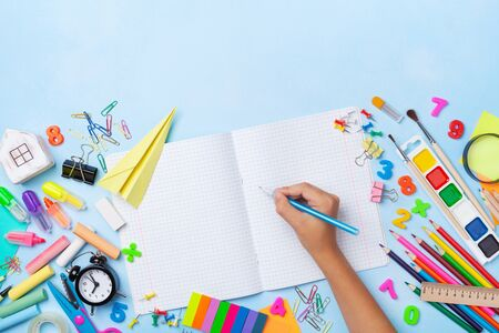 School supplies and stationery with children hand writing in empty notebook top view. Education, learning and back to school concept.