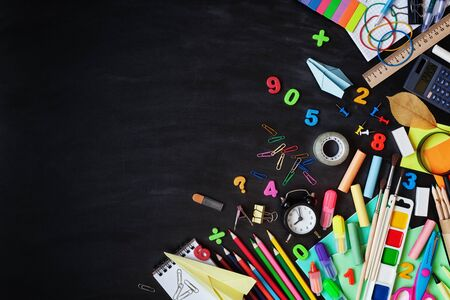 Set of stationery, alarm clock and supplies on blackboard background. Back to school concept. Top view.