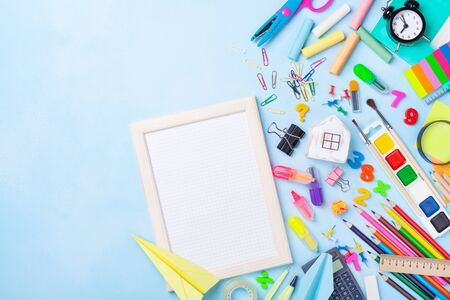 School supplies, stationery and empty frame with squared paper on blue table top view. Education, learning and back to school concept. Imagens