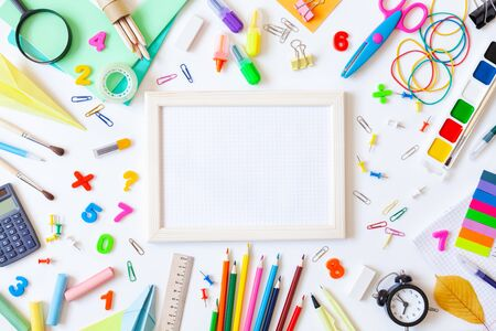 Empty wooden frame with squared paper, alarm clock, different stationery and colorful supplies on white background. Back to school concept. Top view. Imagens