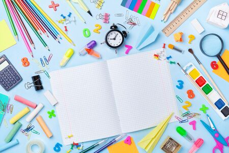 School supplies and stationery with open notebook on blue table top view. Education, learning and back to school concept.