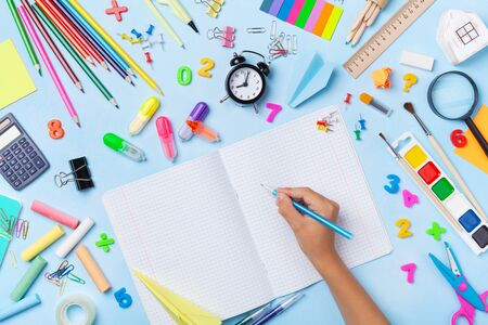 Supplies and stationery with schoolboy hand writing in empty notebook top view. Education, learning and back to school concept.