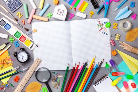Set of school supplies and stationery with open notebook on gray table top view. Education, learning and back to school concept.
