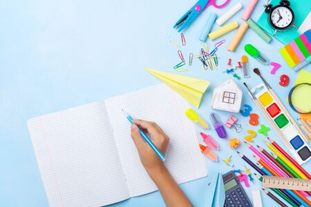 School supplies and stationery with children hand writing in empty notebook on blue table top view. Education, learning and back to school concept.
