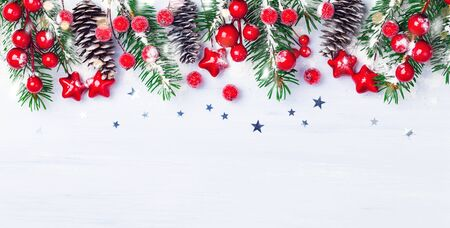 Christmas background with snowy fir branches, cones and red berry. Banner format.