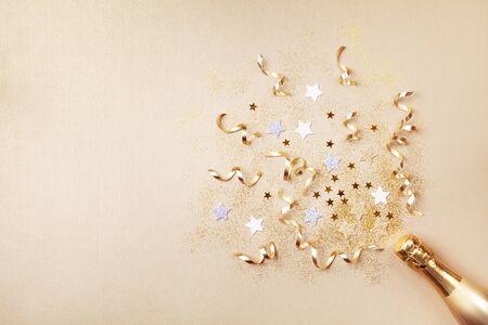 Sektflasche mit Konfettisternen, Glitzer und Party-Streamern auf goldenem Hintergrund. Weihnachts-, Geburtstags- oder Hochzeitskonzept. Flacher Lay-Stil.
