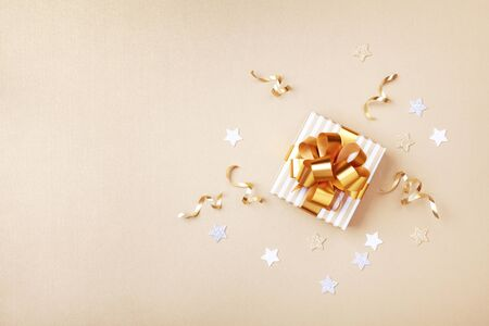 Gift or present box and stars confetti on golden table top view. Flat lay composition for birthday, christmas or wedding. Imagens