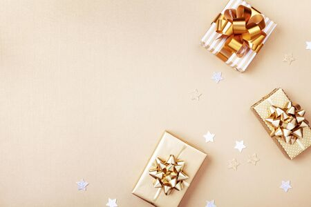 Gift or present boxes and stars confetti on golden table top view. Flat lay composition for birthday, christmas or wedding.