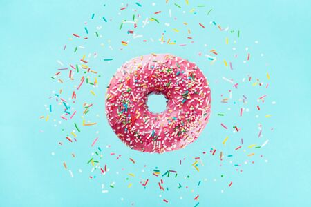 Flying sprinkled pink donut. Sweet doughnut on pastel blue background.