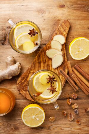 Healing ginger tea in two glass mug with lemon, honey and spices. Autumn hot drink on rustic wooden table top view.