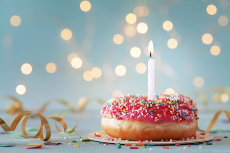 Pink donut and one burning candle against bokeh light background. Happy birthday concept.