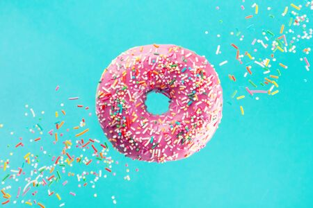 Flying sprinkled pink donut. Sweet doughnut on pastel turquoise background. Imagens