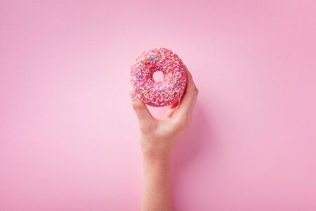 Woman hand holding pink donut or doughnut on pastel background. Flat lay.