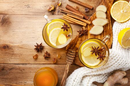 Healing ginger tea in two glass mug in scarf with lemon, honey and spices. Autumn hot drink on rustic wooden table top view. Imagens
