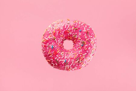 Minimal composition of flying pink donut. Sweet doughnut on pastel background.