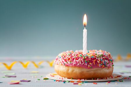Sweet donut and one burning candle. Happy birthday concept. Imagens