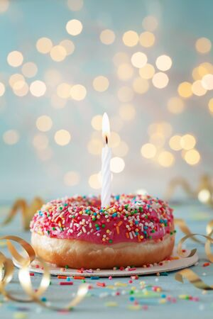 Sweet donut and one burning candle against bokeh light background. Happy birthday concept. Imagens - 129957465