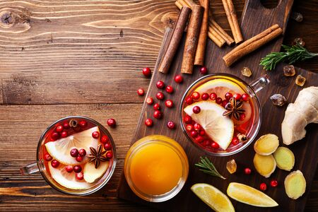 Healing cranberry tea in two glass mug with lemon, honey, ginger and spices. Autumn hot drink on rustic table top view. Imagens - 129957632