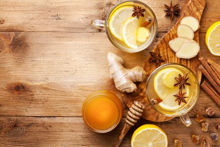 Healing ginger tea in two glass mug with lemon, honey and spices. Autumn hot drink on wooden table top view. Imagens
