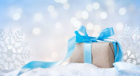Beautiful Christmas gift or present box in snow and decoration against holiday lights background. Imagens