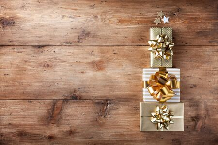 Stack of gift or present boxes in the form of Christmas tree on wooden table top view. Celebration Christmas or New year concept.