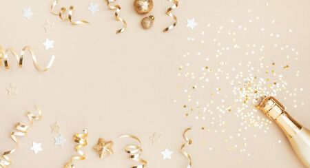 Champagne bottle with confetti stars, holiday decoration and party streamers on gold festive background. Christmas, birthday or wedding concept. Flat lay. Imagens - 129957808