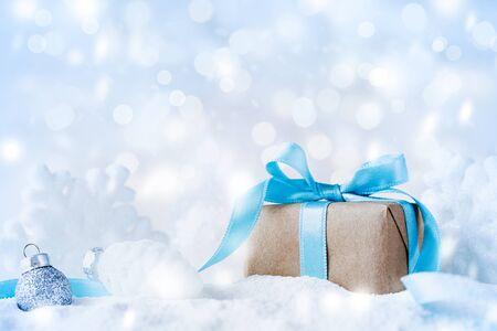 Piękna kompozycja świąteczna z pudełkiem prezentowym lub prezentowym w śniegu i dekoracji na tle świątecznych świateł.