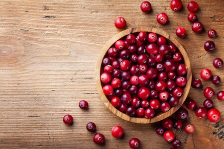 Ripe cranberry in wooden bowl on rustic table top view. Imagens - 129958359