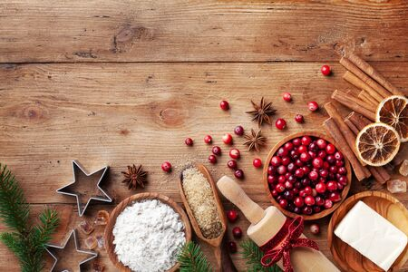Ingredients for cooking Christmas baking. Flour, sugar, butter, cranberry and spices on kitchen wooden table top view. Bakery background. Imagens
