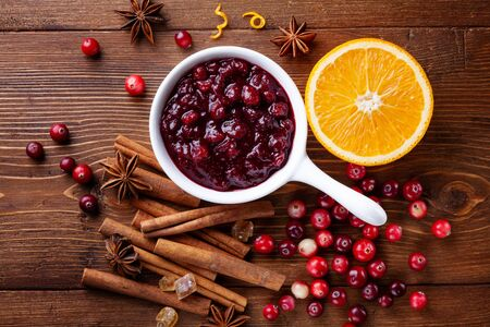 Cranberry sauce in ceramic saucepan with ingredients for cooking on kitchen wooden table from above.