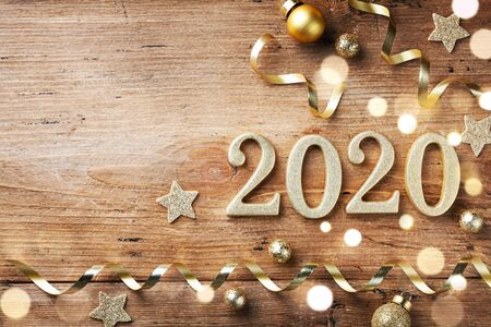 New Year celebration and festive background with golden numbers 2020, confetti stars and Christmas decorations top view. Imagens