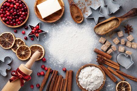 Ingredients for cooking Christmas baking. Flour, sugar, butter, cranberry and spices top view. Bakery background.