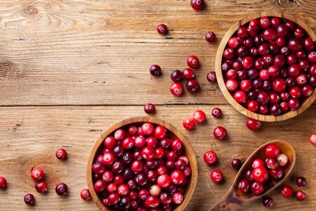Cranberry in wooden bowl on rustic table from above.