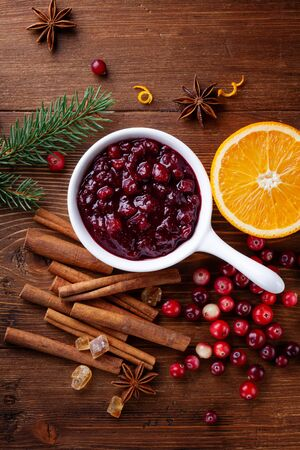 Cranberry sauce in ceramic saucepan with ingredients for cooking decorated with fir tree for Christmas or Thanksgiving day on rustic kitchen table from above.