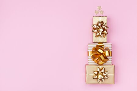 Stack of golden gift or present boxes in the form of Christmas tree on pink background top view. Celebration Christmas or New year concept. Flat lay.