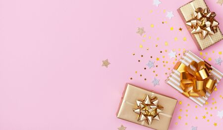 Golden gift or present boxes and star confetti on pink background top view. Festive composition for birthday, christmas or wedding. Flat lay. Imagens - 129959051