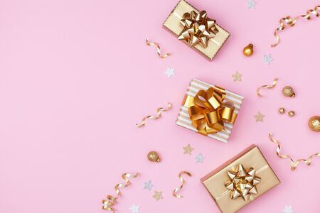 Golden gift or present boxes and Christmas decorations on pink background top view. Flat lay.