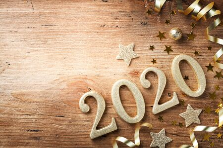 Happy New Year festive background with golden numbers 2020 and Christmas decorations on vintage wooden table top view.