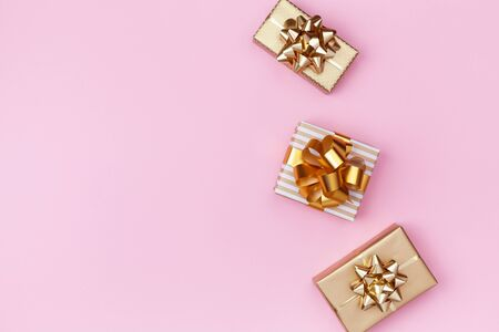 Golden gift or present boxes on pink background top view. Festive composition for birthday, christmas or wedding. Flat lay. Imagens
