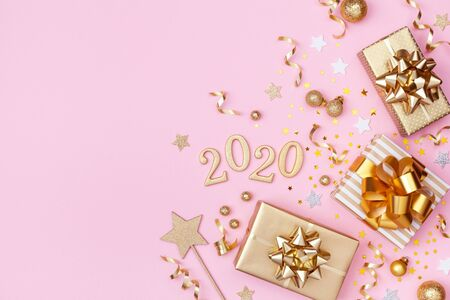 Golden gift or present boxes, 2020 numbers and Christmas decorations on pink background top view. Flat lay. Imagens