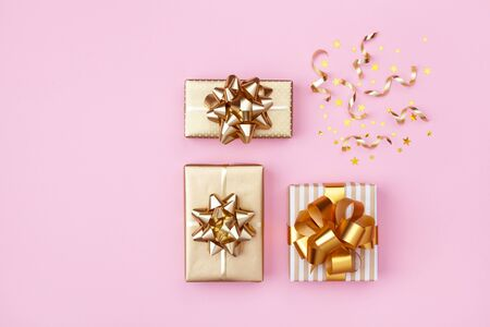 Golden gift or present boxes and star confetti on pink background top view. Festive composition for birthday, christmas or wedding. Flat lay style.