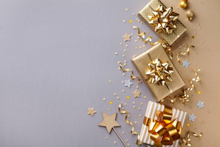 Golden gift or present boxes with golden bows and star confetti on bicolor background top view. Flat lay composition for Christmas card.